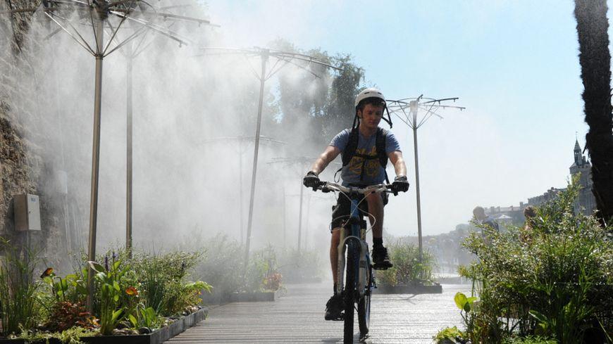 Un jeune garçon passe à vélo sous les brumisateurs de Paris Plages à Paris sur les quais de Seine
