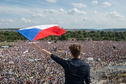 Un manifestant brandit le drapeau tchèque face à l'immense cortège de Prague réclamant la démission du premier ministre tchèque