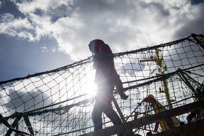 Un migrant débarque du navire de sauvetage de l'ONG Sea Watch 3 battant pavillon néerlandais après son arrivée à quai le 31 janvier 2019 dans le port sicilien de Catane, dans le sud-est de la Sicile.