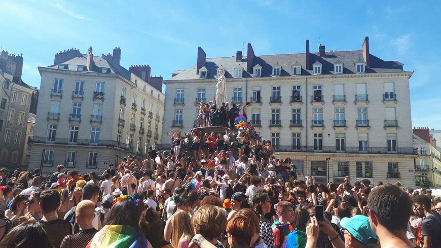 Les participants à la marche des fiertés sur la fontaine de la place Royale à Nantes