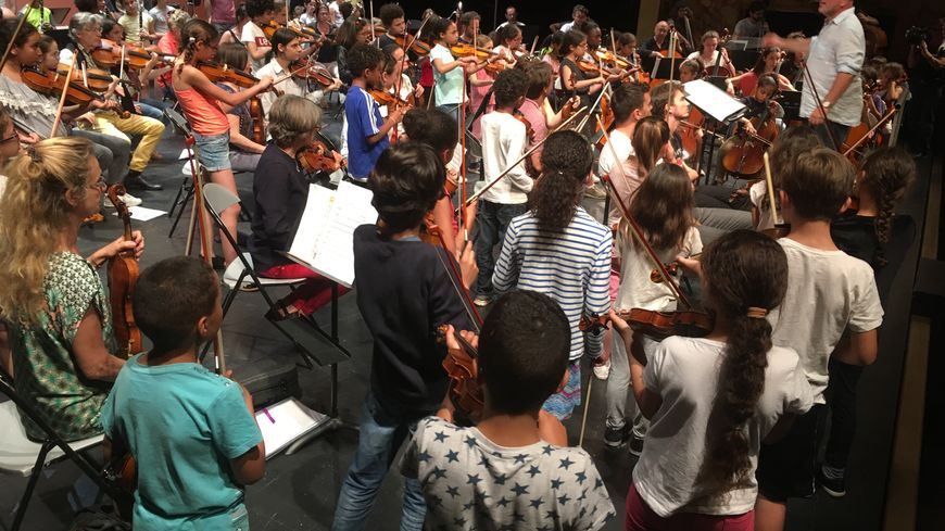 Le chef d'orchestre, Jérôme Pillement, coache 100 enfants sur la scène de l'Opéra-Comédie.