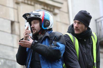 Le journaliste Rémy Buisine pour le média en ligne Brut, à côté d'un manifestant Gilets jaunes
