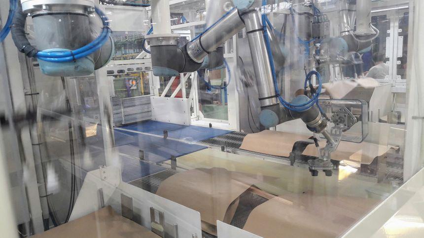 Les bras robotisés sont capables de saisir délicatement les plats en verre Pyrex mais aussi des feuilles de papier cartonnées servant à les amortir avant des les empiler