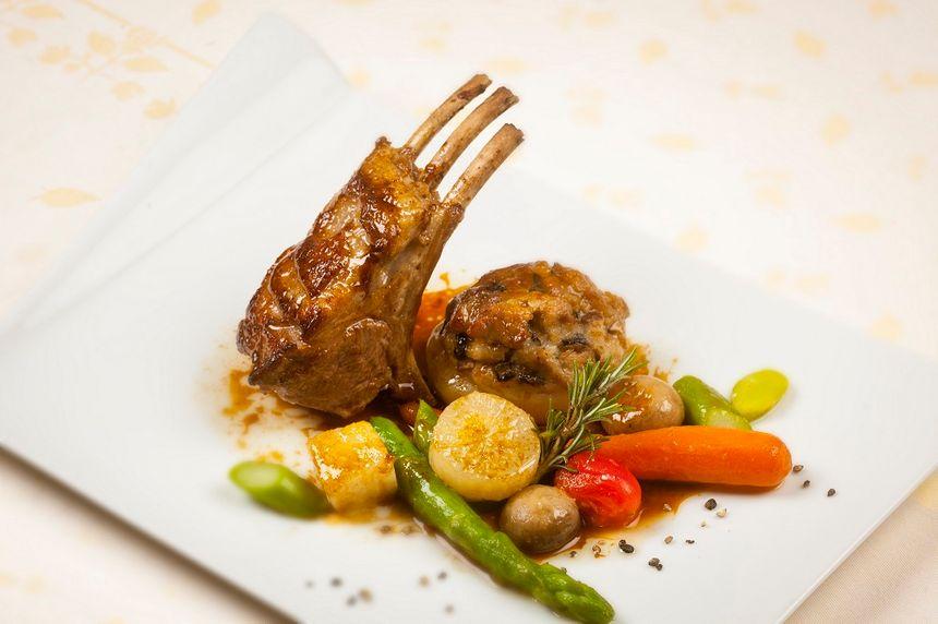 Carré d'agneau rôti au romarin, jus tranché et légumes du moment