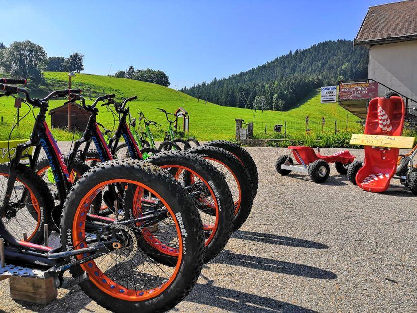 Devant le magasin de location, les VTT de montagne côtoient les bobsleigh à roulettes