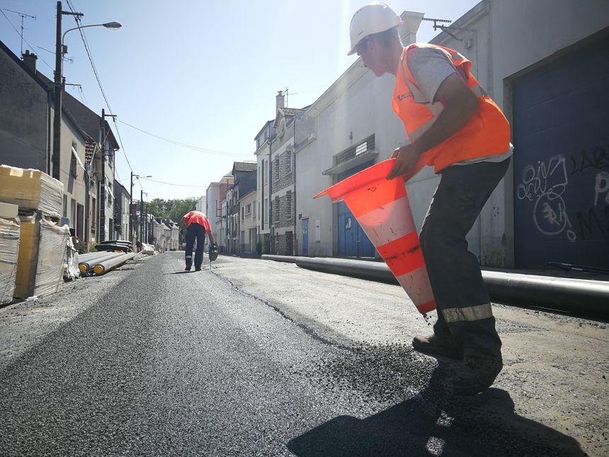 Dans la rue du Général Renault, les ouvriers posent un enrobé bitumineux chaud, ce qui s'ajoute à la canicule.