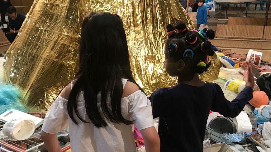 Très concernés, les enfants devisent devant une queue de baleine dorée entourée de déchets ménagers