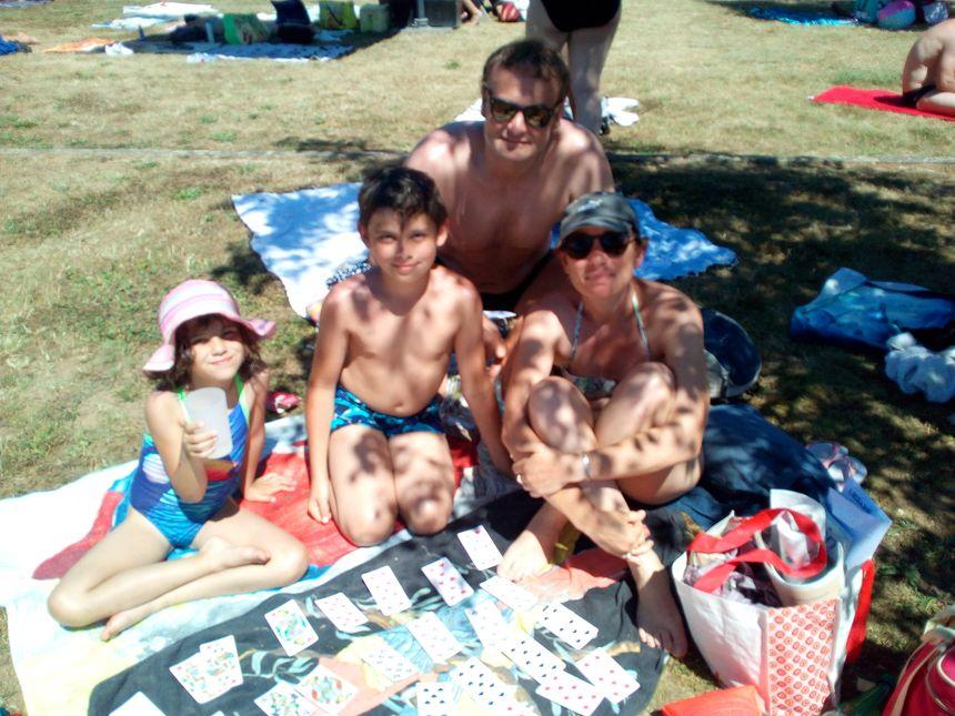 Cette famille a réussi a dénicher un petit coin d'ombre pour jouer aux cartes.