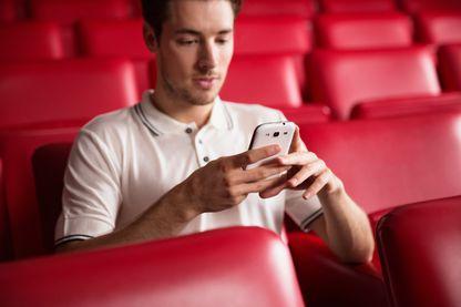 Un homme envoyant un texto au cinéma depuis son smartphone