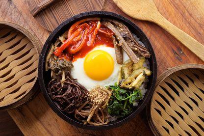Le Bibimbap, mélange de légumes, de viande, de riz d'œuf assaisonné et servi dans un bol, est le plat populaire coréen par excellence.