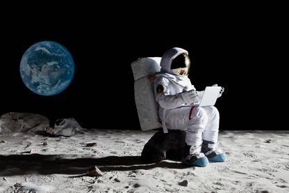 Un astronaute sur la lune assis sur un rocher avec un ordinateur portable.