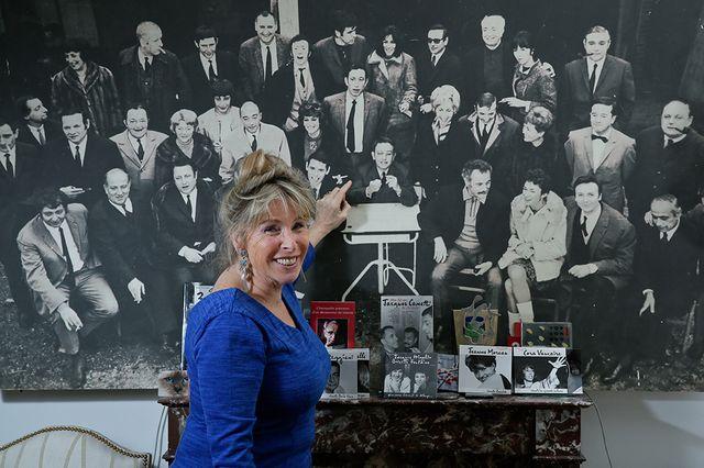 Françoise Canetti devant une photo de son père entouré des artistes qu'il produisait