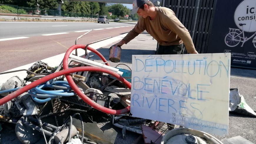 Gaspard Forest sort les déchets de l'eau pour les exposer à la vue des passants