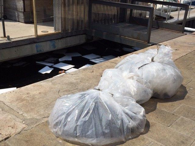 les buvards une fois saturés de produit hydrocarbure sont ramassés et stockés dans ces sacs, et remplacés par de nouveaux sur le plan d'eau