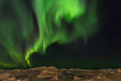 Aurores boréales sur le rivage de la baie gelée de Disko.