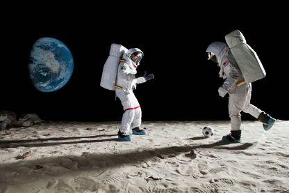 Deux astronautes jouent au football sur la lune.