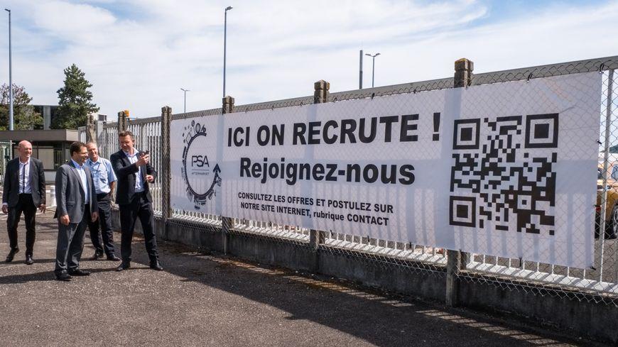 PSA Vesoul recrute 250 à 350 personnes, le directeur du site devant l'une des banderoles qui l'annoncent