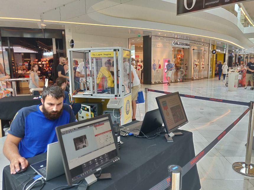Romain Guenard, au premier plan, programme une simulation virtuelle du robot
