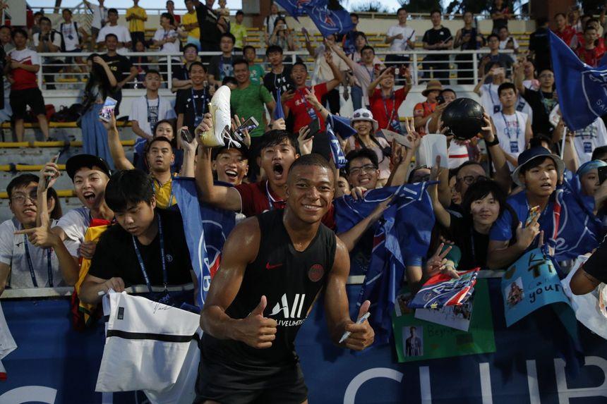 Kylian Mbappé pose devant des supporters locaux après une séance d'entraînement.