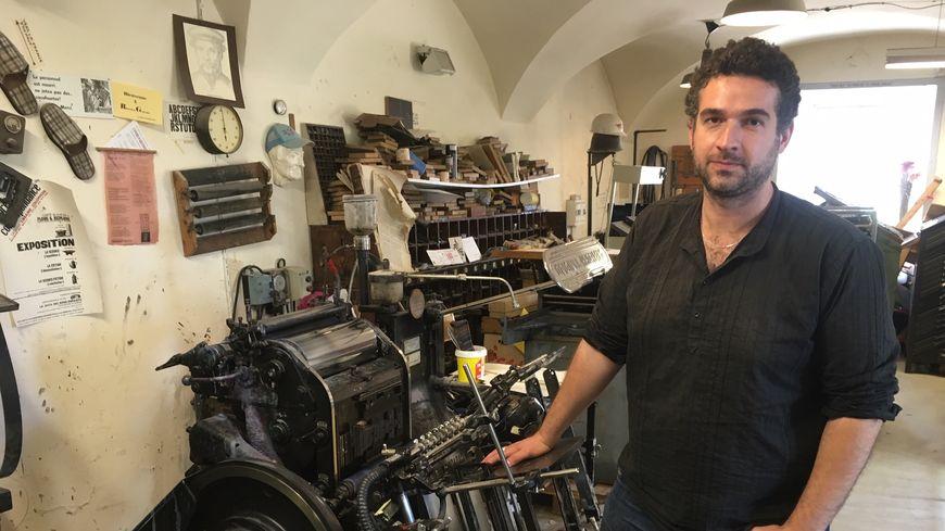 Yoann Martinez, typographe et éditeur, pose devant l'une des vieilles presses Heidelberg.