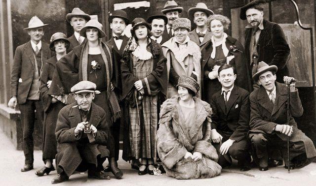 Man Ray (accroupi à gauche) et Kiki de Montaparnasse (debout derrière lui), devant le Jockey Club. On reconnait au premier rang à droite (avec la canne), Jean Cocteau
