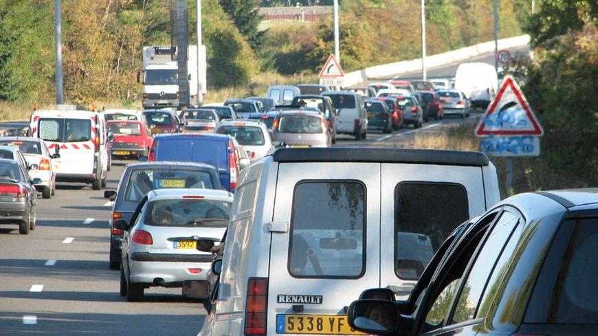 Vue arrière de files de voitures sur une autoroute, dans une courbe, sous le soleil