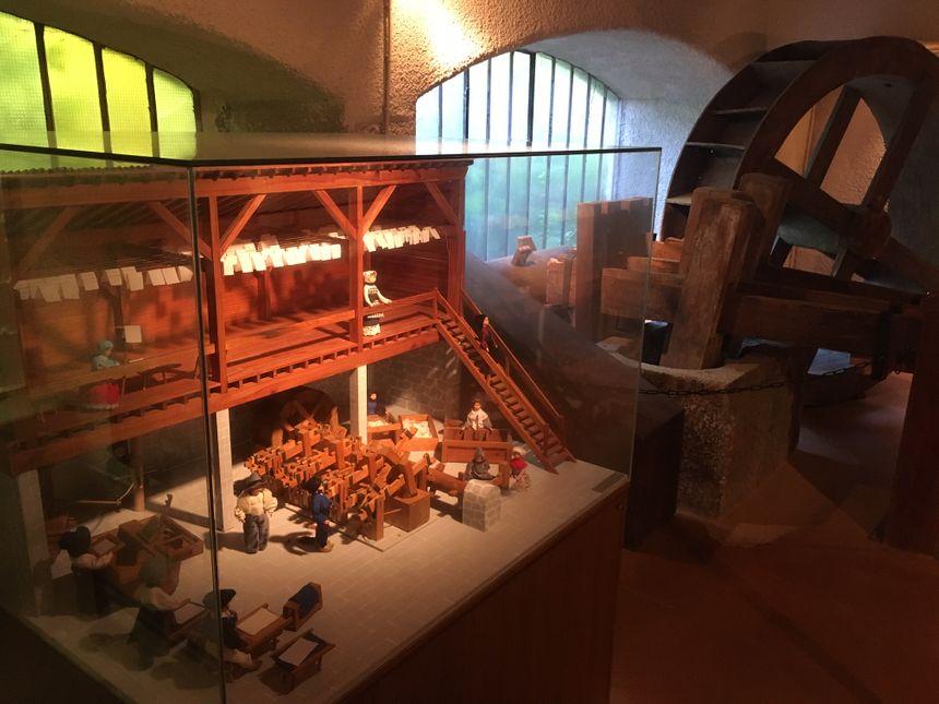 Maquette d'un atelier de fabrication du papier au moyen-âge et, au fond, une pile à maillets.