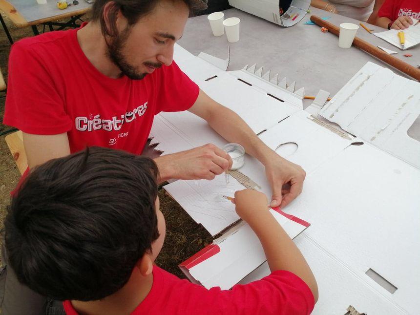 Noah et Loïc s'affairent sur un projet de masque géant de dinosaure