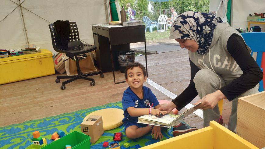 Nadia fait la lecture à Sami, son fils de trois ans, dans la bibliothèque éphémère du quai des sports, à Bordeaux.