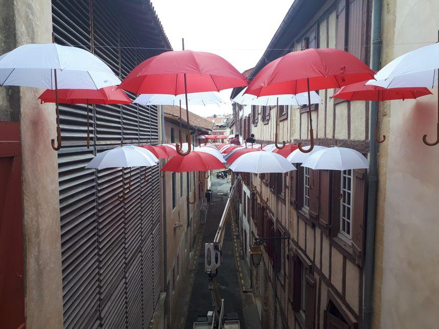 Les parapluies sont suspendus à 8 mètres au-dessus du sol. Le câble est fixé aux parois des immeubles, avec l'accord des propriétaires.