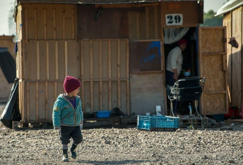 Un enfant devant une cabine en bois, au camp de migrants et de réfugiés de Grande-Synthe, dans le Nord de la France, le 4 octobre, 2016.