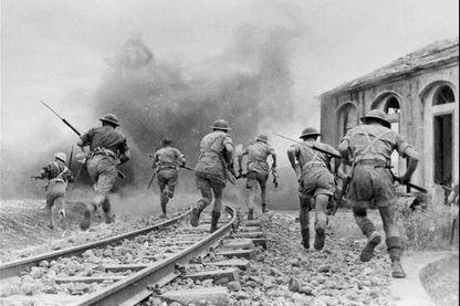 Photo prise en août 1943 de troupes britanniques de la 8ème Armée, sous le commandement du général Montgommery, avançant lors de combats en Sicile, durant la seconde guerre mondiale. Après deux semaines de combats, les Alliés seront maîtres de l'île.