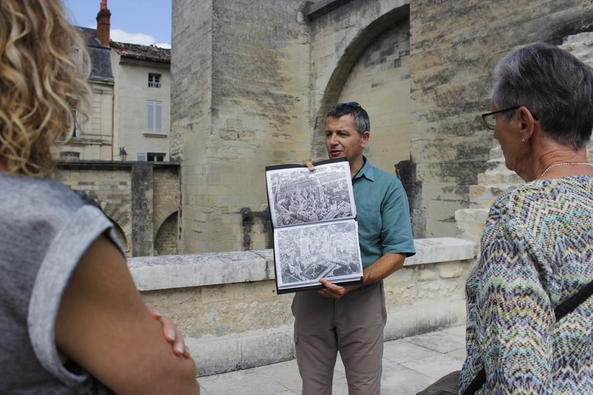 Le guide Christophe Metreau montre aux visiteurs des iconographies pour se représenter la cathédrale avant sa reconstruction