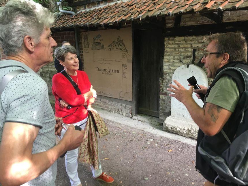 Janet et son mari, devant l'entrée de la grotte, avec Gilles Prilaux, archéologue (à droite). - Radio France