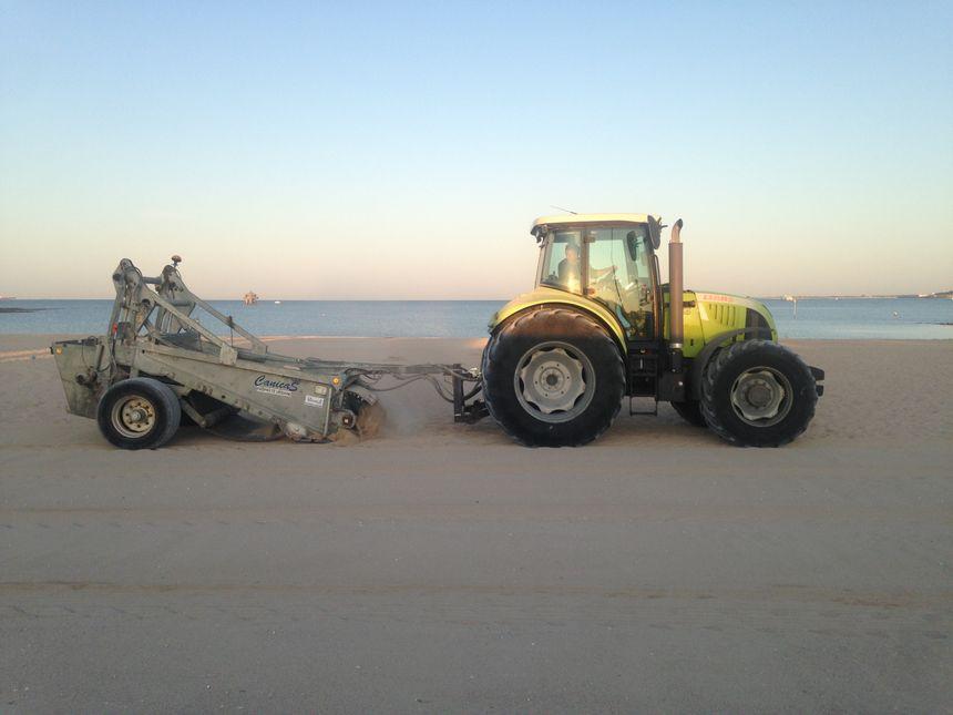 Le tracteur de plage tamise le sable pour enlever les déchets enfouis