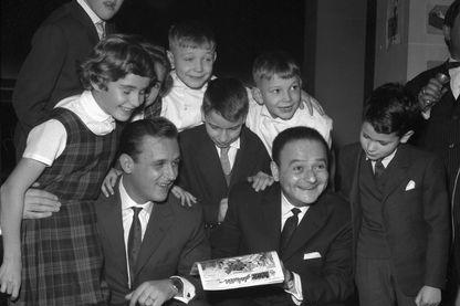 """René Goscinny (D), le père d'Astérix le Gaulois, de Lucky Luke, d'Iznogoud le vizir, et son complice, le dessinateur Albert Uderzo, posent au milieu du jury d'enfants pour la remise du """"Prix Collégien"""" à Paris en 1962."""