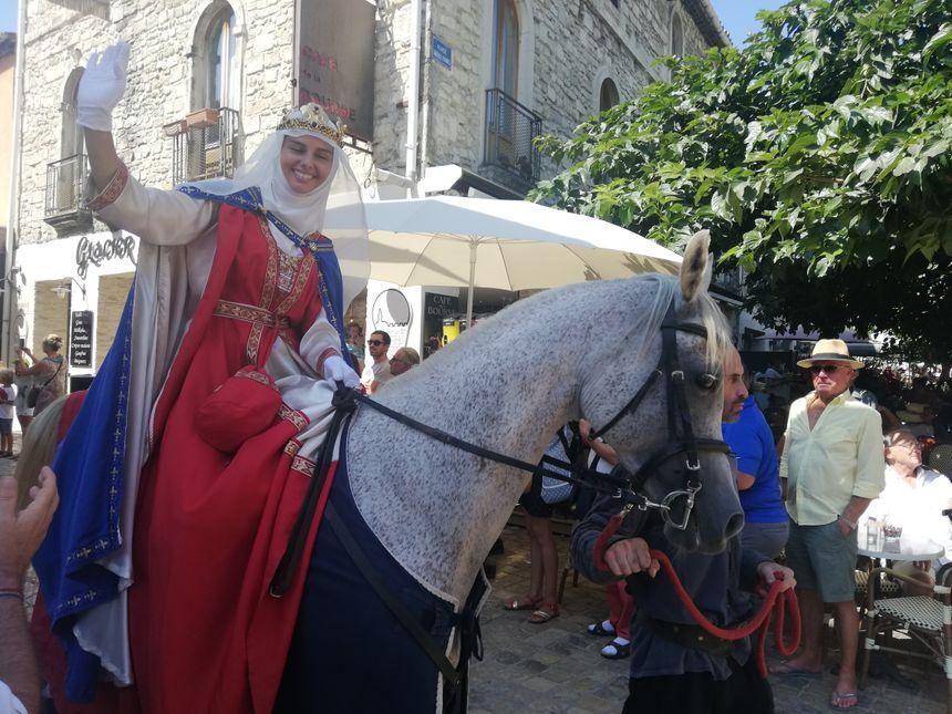 La reine salue la foule pendant le défilé historique de la fête de la Saint-Louis à Aigues-Mortes