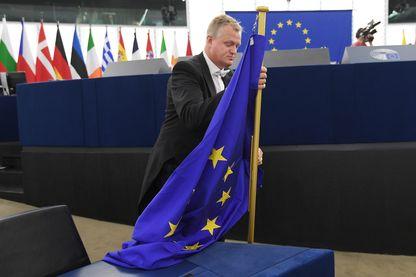 Un huissier de justice porte un drapeau européen à la veille de la session inaugurale du Parlement européen après les élections européennes.