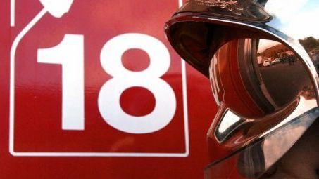 Un casque de pompier devant un camion avec le logo 18