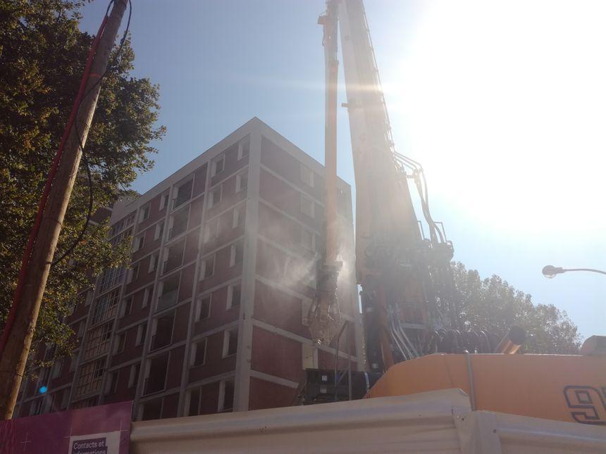 Le bras mécanique commence par casser les pierres du toit d'un des bâtiments de la cité. Pas d'explosion donc mais les habitants n'en sont pas moins impressionnés.