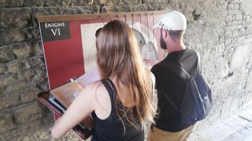 Deux visiteurs tentent de résoudre l'énigme numéro 6 de l'escape game dans les arènes de Nîmes