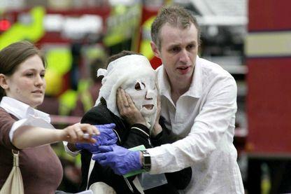 """Une femme blessée victime de l'explosion est aidée à la station de métro """"Aldgate Station"""", le 7 juillet 2005 à Londres"""
