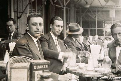 Le poète Robert Desnos (à l'avant-plan à gauche) est assis à une table sur une terrasse de café en 1920.