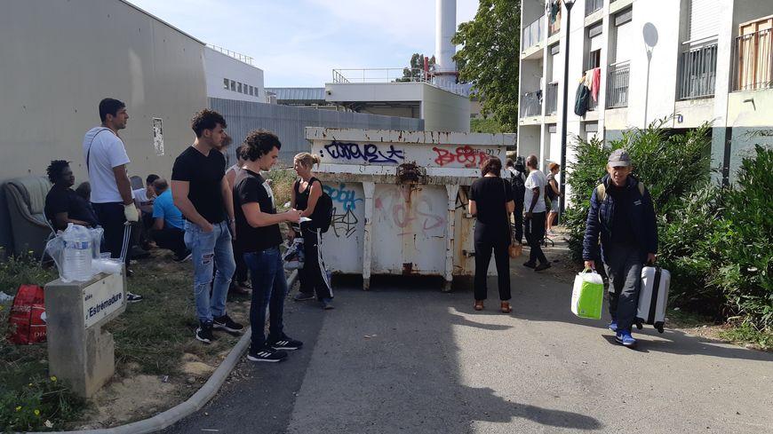 Les migrants se sont retrouvés au pied de l'immeuble, ce vendredi matin.