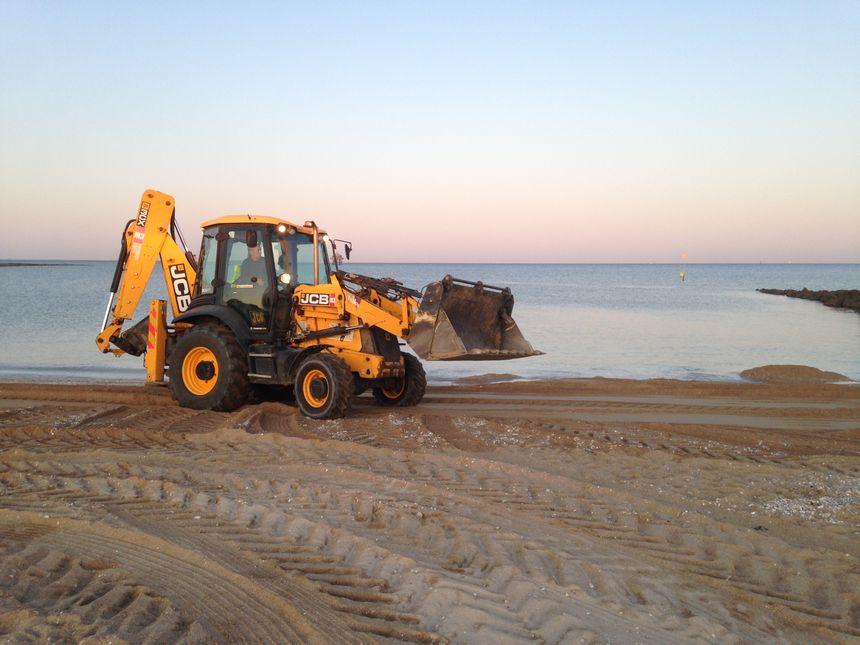 Un bulldozer comblant les trous sur la plage des Minimes