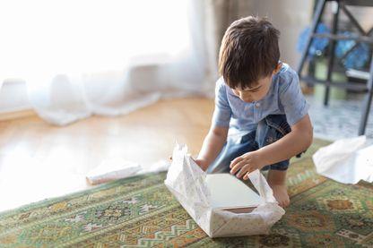Enfant déballant un cadeau (image d'illustration)