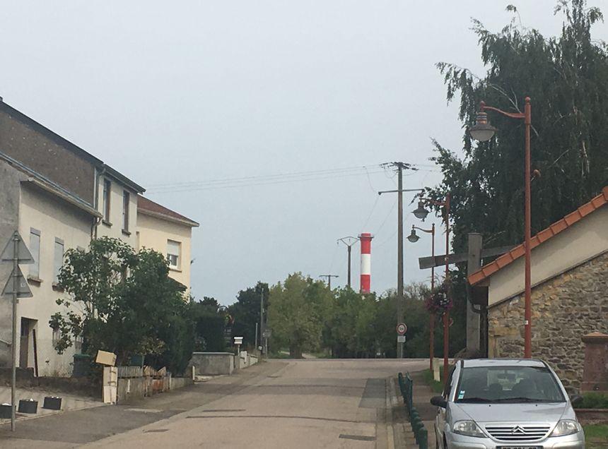 Dans les rues d'Illange, on aperçoit la grande cheminée rouge et blanche de l'usine Knauf, à quelques centaines de mètres.