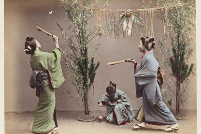 Jeunes filles jouant a la balle (temari) et au volant avec des raquettes en bois (hanetsuki), a l'occasion du nouvel an, avec kadomatsu (decoration de pin et bambou) et shimenawa (fin XIXe)
