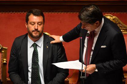 Le Premier ministre italien Giuseppe Conte touche l'épaule du vice-Premier ministre et ministre de l'Intérieur Matteo Salvini alors qu'il prononce un discours devant le Sénat italien à Rome le 20 août 2019.