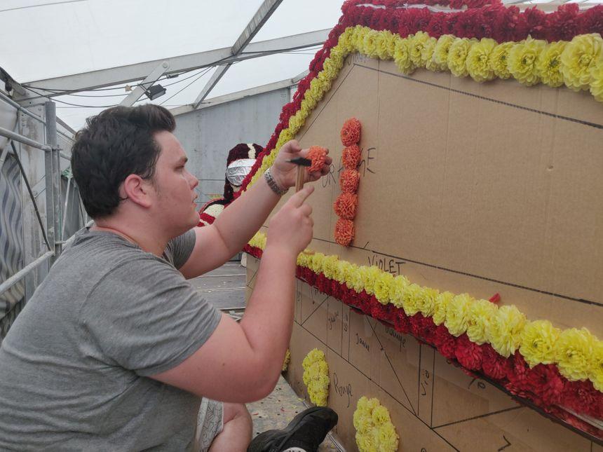 Une fois préparées, les fleurs sont fixées sur les chars par les bénévoles